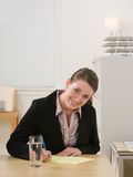 Businesswoman writing on legal pad taking notes. Confident businesswoman writing on legal pad taking notes Royalty Free Stock Photography