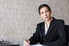 Businesswoman writing letter at desk Stock Image