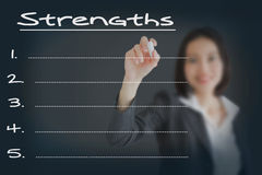 Businesswoman writing list of business strength. Beautiful businesswoman writing list of business strength Stock Photos