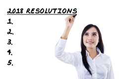 Businesswoman writing a list resolutions for 2018 Royalty Free Stock Photo