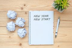 Businesswoman writing New Year New Start with notebook, crumbled paper and black coffee cup on table. Creative, Idea, Resolution,. Solution, Strategy and royalty free stock image