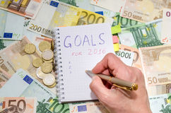 2017 businesswoman writing new years resolution list against euro banknote Stock Photo