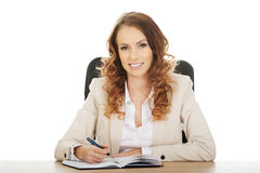 Businesswoman writing note by a desk. Royalty Free Stock Photos