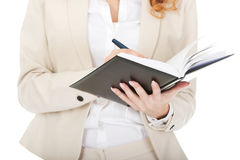 Businesswoman writing in a note. Stock Images