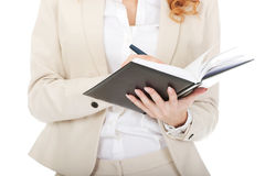 Businesswoman writing in a note. Royalty Free Stock Photos