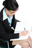 Businesswoman writing in notebook Stock Image