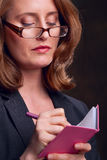 Businesswoman writing in notebook Stock Images