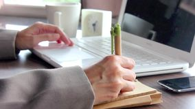 Businesswoman Writing On Notebook and Working With Laptop in Office. stock footage