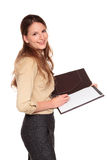 Businesswoman - writing on notepad. Isolated studio shot of a Caucasian businesswoman smiling at the camera while writing on a business notepad Stock Photography