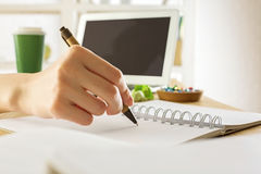 Businesswoman writing in notepad. Close up of businesswoman writing in notepad placed on wooden desktop with blank laptop, supplies and other items. Mock up stock photo