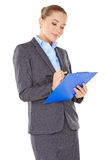 Businesswoman writing notes on a clipboard Stock Images
