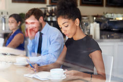 Businesswoman Writing Notes In Coffee Shop Royalty Free Stock Photography