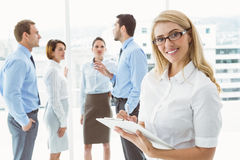 Businesswoman writing notes with colleagues behind Stock Image
