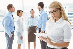 Businesswoman writing notes with colleagues behind Stock Photo