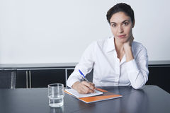 Businesswoman Writing Notes At Conference Table Stock Photography