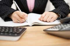 Businesswoman writing notes at her desk Stock Images