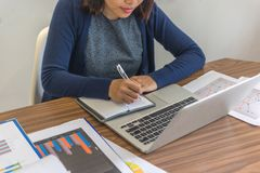 Businesswoman writing notes in her office royalty free stock photo