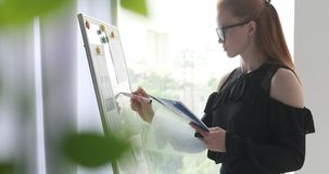Businesswoman writing notes on office whiteboard stock footage