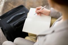Businesswoman Writing Notes on Trip. High angle close up of unrecognizable young businesswoman writing in notebook while waiting for business travel with Royalty Free Stock Images