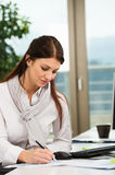 Businesswoman Writing In Office Stock Photography