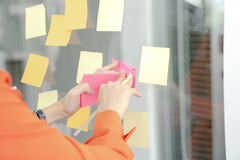 Businesswoman Writing On Colorful Sticky Note Paper In Business Office Royalty Free Stock Photography