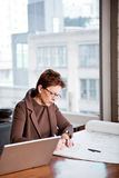 Businesswoman writing on a paper stock photo