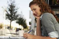 Businesswoman Writing On Paper At Outdoor Cafe. Side view of young businesswoman writing on paper at outdoor cafe Royalty Free Stock Image