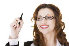 Businesswoman writing with pen on abstract screen. Royalty Free Stock Image