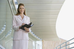 Businesswoman Writing In Planner. Portrait of a happy young businesswoman writing in planner Royalty Free Stock Image