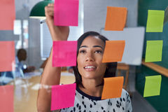 Businesswoman writing on post it note Stock Photography