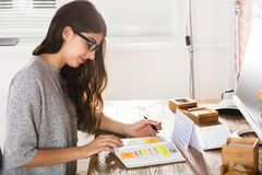 Businesswoman Writing Schedule In Diary. Young Businesswoman Writing Schedule In Diary With Calendar On Desk stock images