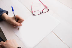Businesswoman writing on sheet of paper Stock Image