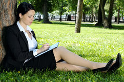 Businesswoman writing something. To diary, sitting on green grass in park Stock Photo
