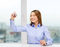 Businesswoman writing something in the air. Office, business, technology concept - businesswoman writing something in the air with marker Stock Images