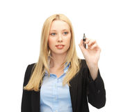 Businesswoman writing something in the air. With marker Stock Images