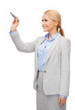 Businesswoman writing something in air with marker. Office, business and new technology concept - smiling businesswoman writing something in the air with marker Stock Image