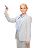 Businesswoman writing something in air with marker. Office, business and new technology concept - smiling businesswoman writing something in the air with marker Royalty Free Stock Photos