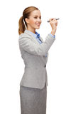 Businesswoman writing something in air with marker Royalty Free Stock Image
