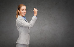 Businesswoman writing something in air with marker. Office, business and new technology concept - smiling businesswoman writing something in the air with marker royalty free stock photo