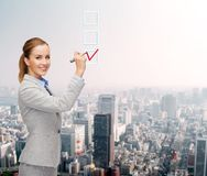Businesswoman writing something in air with marker. Office, business and new technology concept - smiling businesswoman writing something in the air with marker Royalty Free Stock Photography