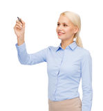 Businesswoman writing something in air with marker. Office, business and new technology concept - smiling businesswoman writing something in the air with marker Royalty Free Stock Image