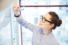 Businesswoman writing something on whiteboard Royalty Free Stock Images
