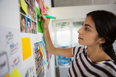 Businesswoman writing on sticky note at office. Young businesswoman writing on sticky note at creative office Stock Photography