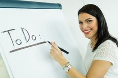 Businesswoman writing todo onto a white writing board Royalty Free Stock Photography