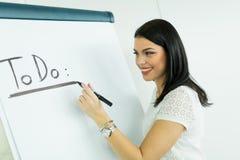 Businesswoman writing todo onto a white writing board Royalty Free Stock Photos