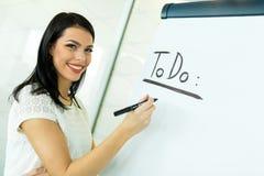 Businesswoman writing todo onto a white writing board Stock Photo