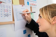 Businesswoman writing on weekly time sheet Royalty Free Stock Photo