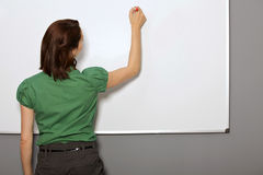 Businesswoman writing on whiteboard in office Royalty Free Stock Images