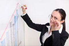 Businesswoman writing on the witeboard. A business woman is drawing a chart/ diagram on the whiteboard Royalty Free Stock Photos