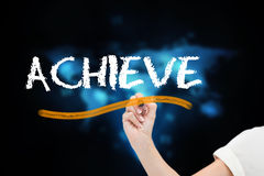 Businesswoman writing the word achieve Royalty Free Stock Photography